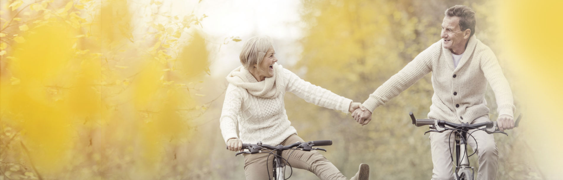 A couple with healthy teeth laughs while riding bikes.